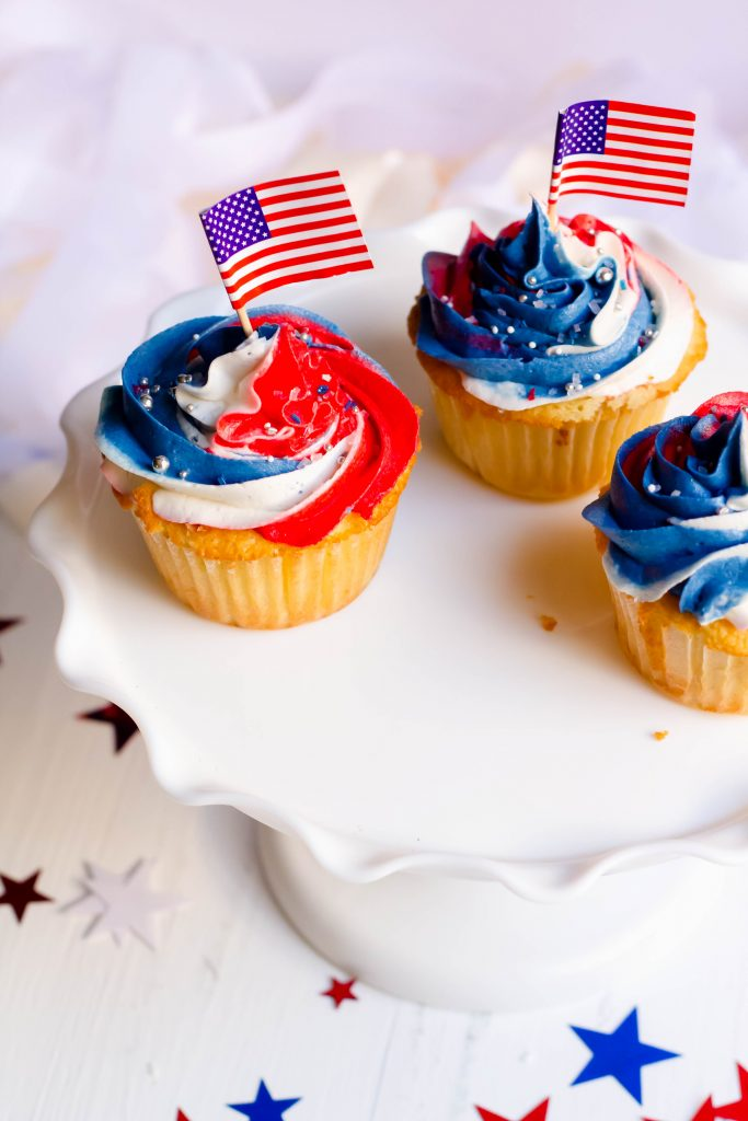 USA cupcakes with buttercream swirls and USA flags.